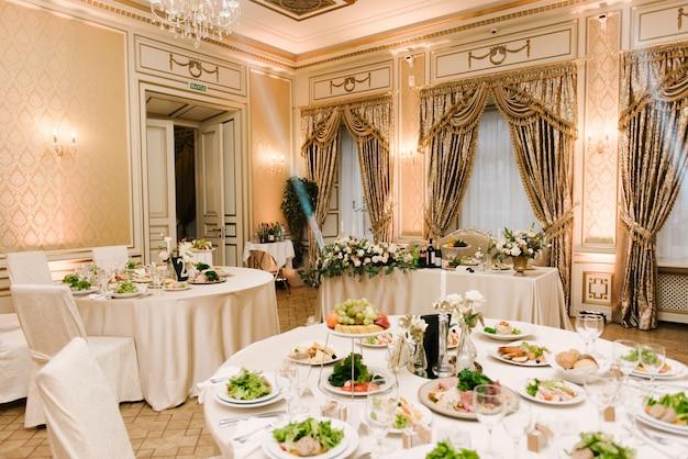 De ronde witte tafel is gevuld met een grote hoeveelheid eten en diverse snacks in een luxe interieur, mooie portie van de vakantietafel
