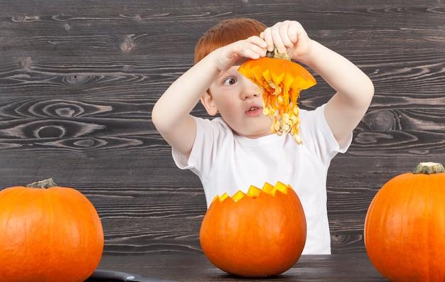 De roodharige jongen neemt het deksel van de gesneden pompoen terwijl hij de pompoen klaarmaakt voor halloween