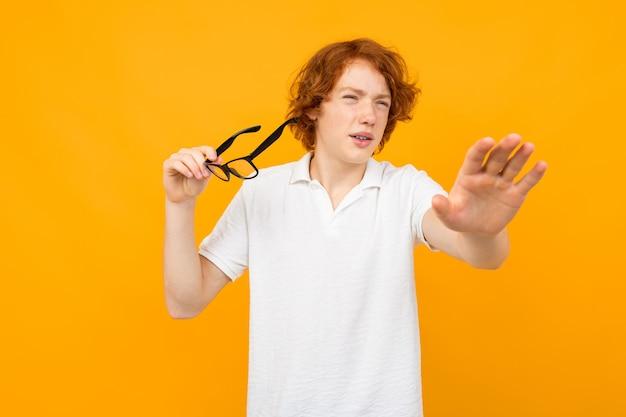 De roodharige kerel in een wit overhemd loenst holdingsglazen in zijn hand op een geel