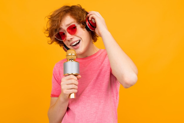 De roodharige kerelzanger in hoofdtelefoons zingt op geel