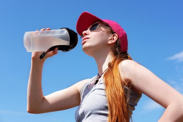 De roodharige magere vrouw in roze glb is drinkwater na jogging, de zomer