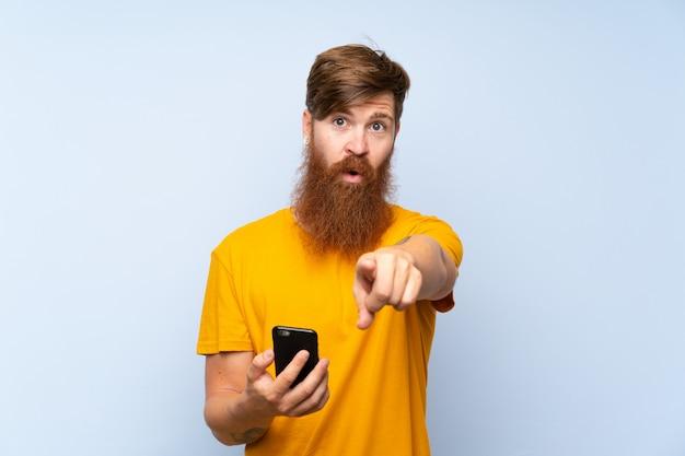 De roodharigeman met lange baard met mobiel over geïsoleerde blauwe muur richt vinger op u met een zekere uitdrukking
