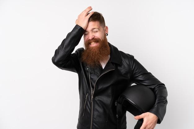 De roodharigemens die met lange baard een motorfietshelm over geïsoleerde witte muur houden die twijfels hebben met verwart gezichtsuitdrukking