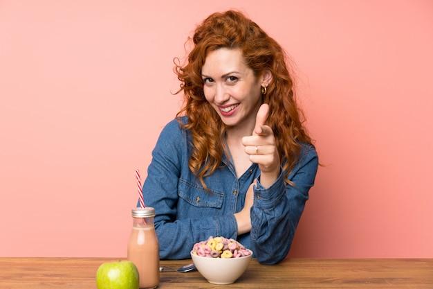 De roodharigevrouw die ontbijtgraangewassen en fruit hebben richt vinger op u