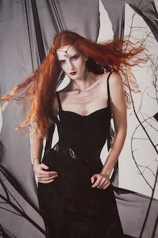 De roodharigevrouw een heks wacht op halloween. roodharige vrouwelijke zwarte magiër