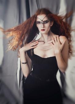 De roodharigevrouw een heks wacht op halloween