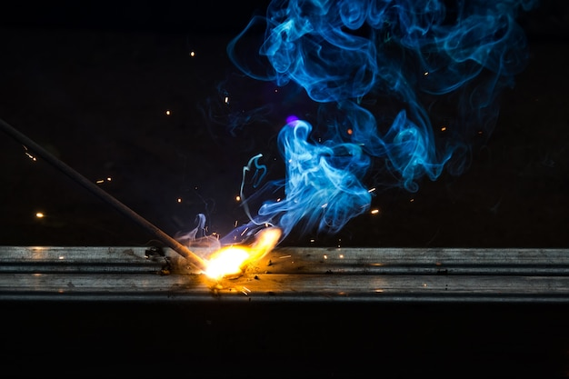 De rook en de vlam van het lassen werken op donkere achtergrond