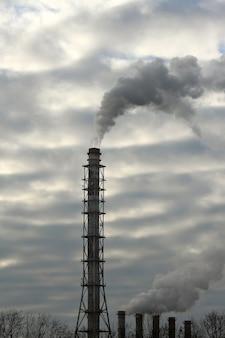 De rook uit de schoorsteen van een industriële onderneming in de lucht