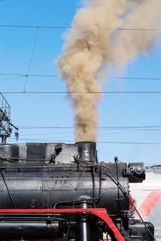 De rook uit de schoorsteen van een stoomlocomotief