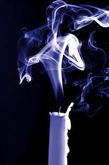 De rook van een gedoofde kaars op zwarte ondergrond