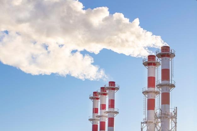 De rookstapel van de fabrieksinstallatie over blauwe hemel. thermische condenserende energiecentrale. energieopwekking en luchtverontreiniging industriële scène