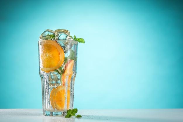 De roos exotische cocktail en fruit op de blauwe muur