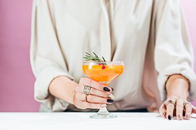 De roos exotische cocktails en fruit en vrouwelijke hand