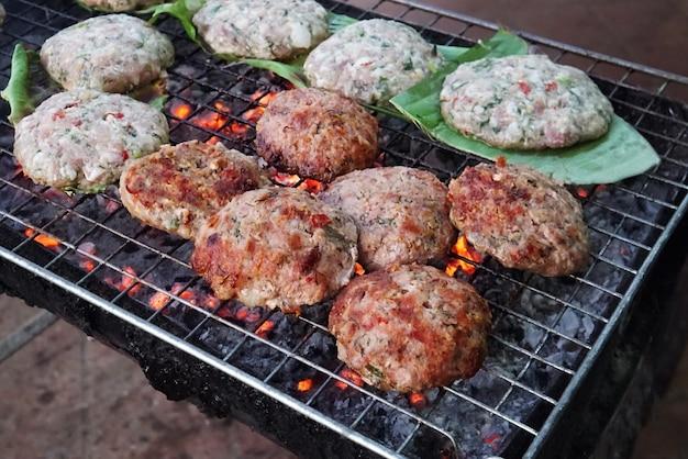 De rossig gebakken schnitzels op een groen blad worden op straat op een grill gebakken. straatvoedsel in azië. voorbereiding van runderkotelet met kruiden op de grill voor hamburgers.
