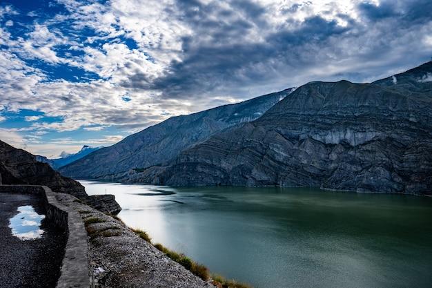 De rotsachtige bergen en het groene meer onder de bewolkte hemel