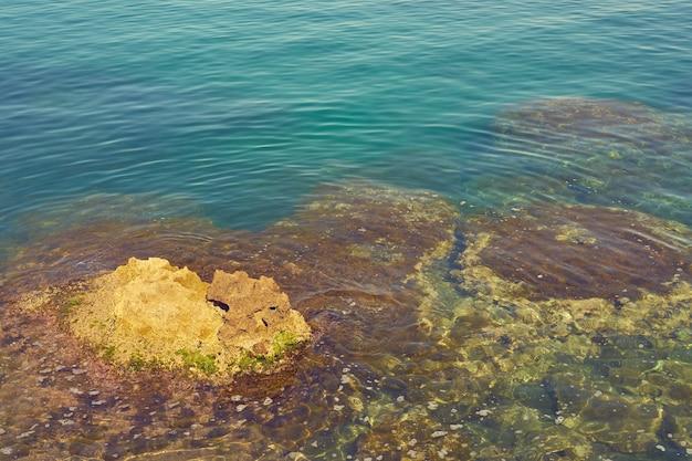 De rotsachtige kust van de middellandse zee met turkoois water