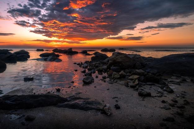 De rotsen bij de zee met avondrood
