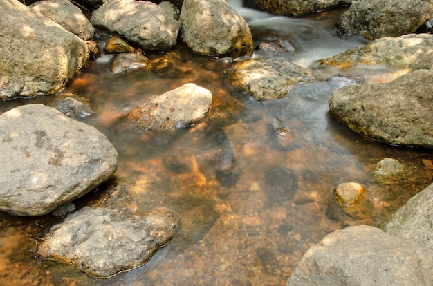 De rotsen die bij de waterval stromen.