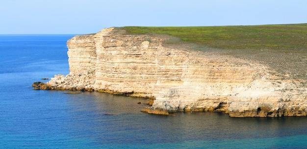 De rotsen van de zwarte zee bij kustlijn met duidelijke blauwe wateren en blauwe hemel