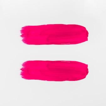 De roze abstracte slagen van de waterverfborstel op witte achtergrond