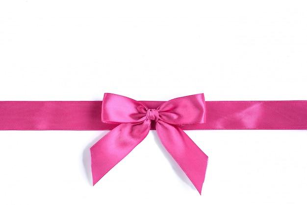 De roze boog van het satijnlint die op witte achtergrond wordt geïsoleerd.