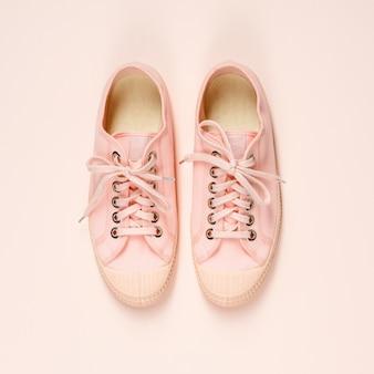 De roze canvastennisschoenen op roze vloer, sluiten omhoog
