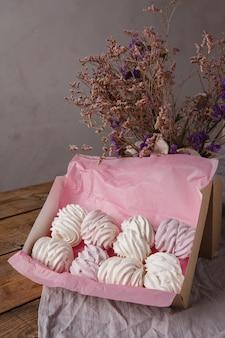 De roze en witte zelfgemaakte meringue marshmallow zephyr op een rustieke houten tafel. zelfgemaakte gezonde snoepjes, heerlijk dessert, natuurlijke marshmallow.
