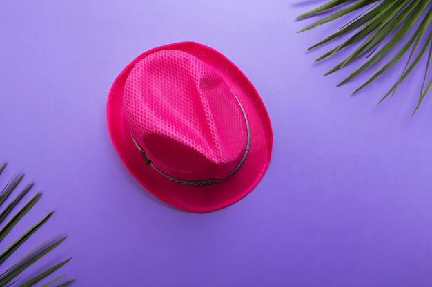 De roze hoed van de manierzomer die op de violette of purpere achtergrond, het concept van de strandzomer en de vlakke vakantie van het vakantieconcept wordt geïsoleerd lag