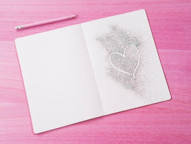 De roze houten achtergrond met schittert blocnote en hart