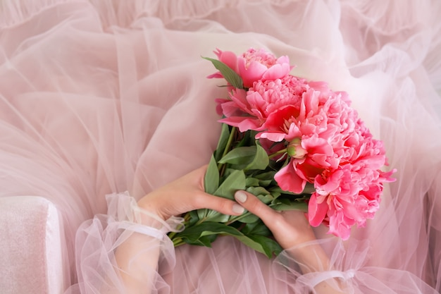 De roze pioen bloeit boeket in vrouwelijke handen