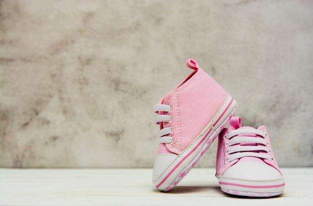 De roze tennisschoenen van het babymeisje, sportschoenen sluiten omhoog newbord, moederschap, zwangerschapsconcept met exemplaarruimte.