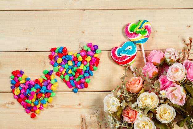 De rozenbloemen met hart vormen suikergoed op houten achtergrondpastelkleurtoon