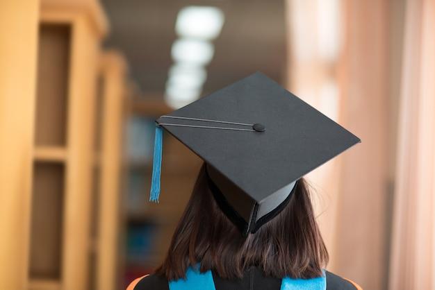 De rug van de afgestudeerden, draag de jurk zwarte hoed en blauwe kwast