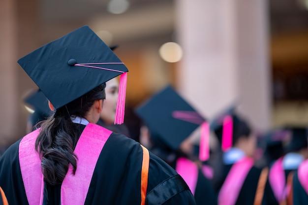 De rug van de afgestudeerden loopt om de diploma-uitreiking op de universiteit bij te wonen