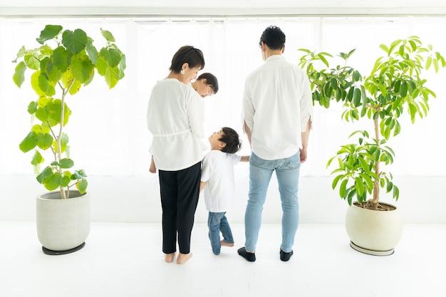 De rug van een familie die zij aan zij bij het raam staat