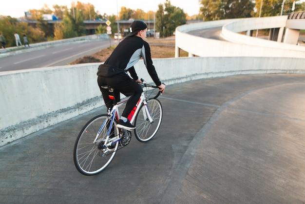 De rug van een fietser is op weg naar buiten de parkeerplaats