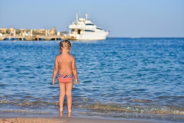 De rug van een klein meisje in een badpak op het strand, een jacht op zee