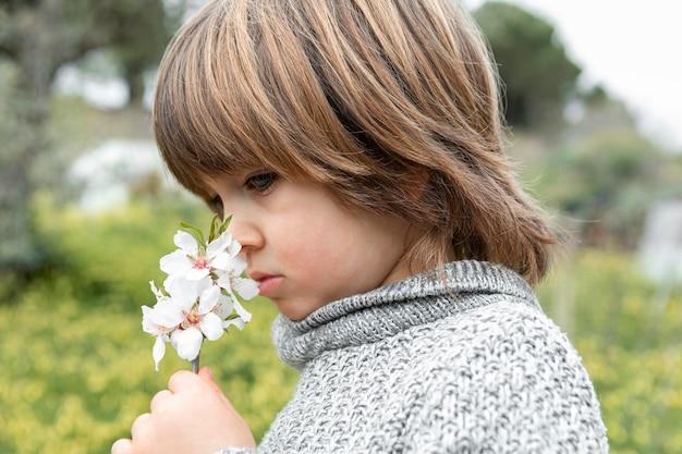 De ruikende bloem van de jongen