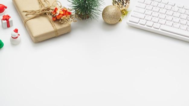 De ruimtedesktop van het bureauwerk met kerstmisdecoratie op witte achtergrond