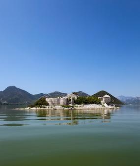 De ruïnes van een gevangenis op een eiland in het skadarmeer. op de achtergrond zijn bergen geplaatst. montenegro.