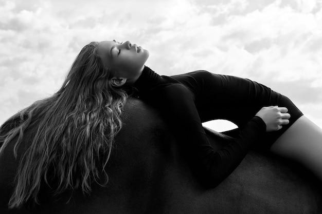 De ruiter van het meisje ligt gebogen op een paard in het veld. mode portret van een vrouw en de merries zijn paarden in het dorp in de lucht. de blondevrouw ligt en droomt op een paard, mooi meisjeslichaam