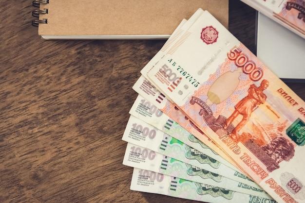 De russische bankbiljetten van het roebelgeld op een houten bureau met een notitieboekje.
