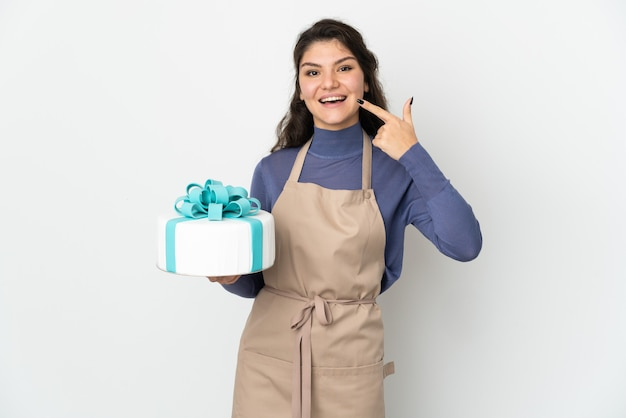De russische chef-kok die van het gebakje een grote die cake houdt op witte muur wordt geïsoleerd die duimen op gebaar geeft