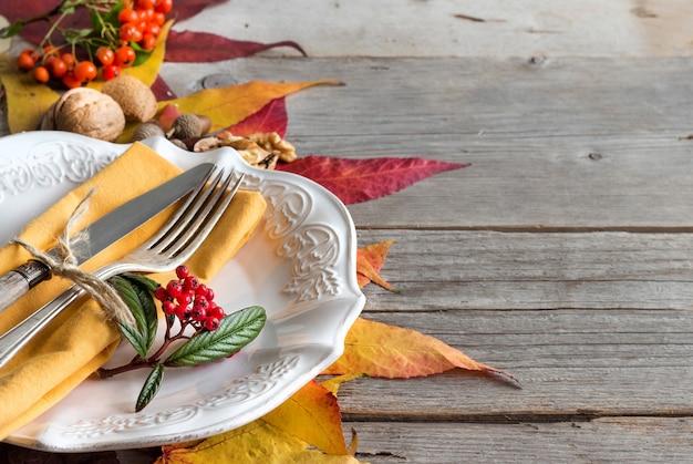 De rustieke lijst die van de herfst met noten en bladerengrens op een houten lijst met exemplaar ruimte dichte omhooggaand plaatst
