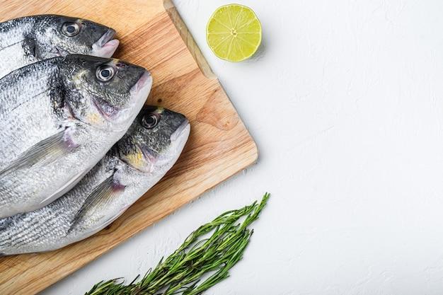 De ruwe dorada of de zeebrasem vissen plaatsten op hakbord met kruiden voor grill ongekookt op witte geweven hoogste mening als achtergrond met ruimte voor tekst.