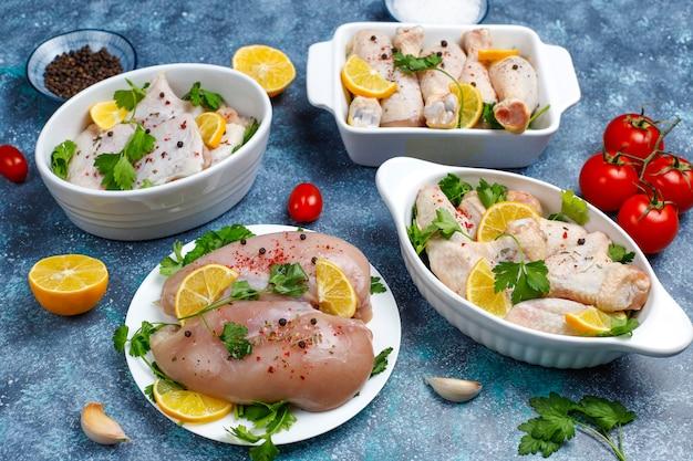De ruwe filet, de dij, de vleugels en de benen van het kippenvlees met kruiden, kruiden, citroen en knoflook op donkerblauwe achtergrond. bovenaanzicht