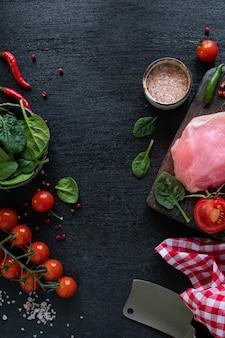 De ruwe filet van turkije klaar voor het roosteren. kipfilet op een houten snijplank met cherrytomaatjes, hete peper, spinaziebladeren en greens. kopie ruimte. bovenaanzicht. verticale foto