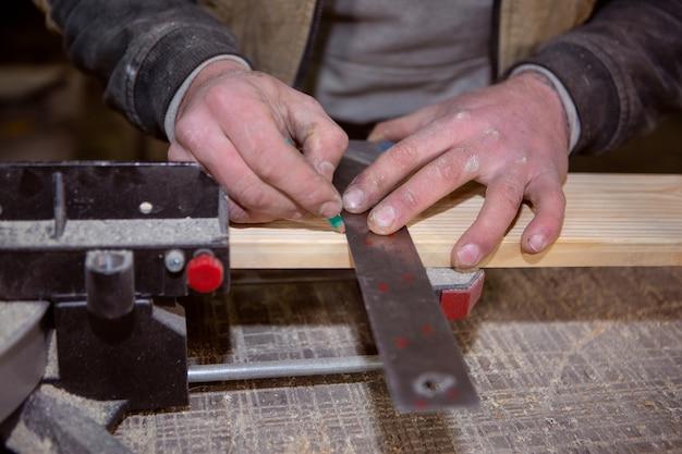 De ruwe handen van de timmerman tekenen met een potlood en een vierkant een lijn op een houten bord.