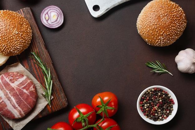 De ruwe kotelet, de tomaten, de sla, het broodje, de kaas, de komkommers en de ui van hamburgeringrediënten op roestige achtergrond