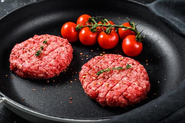De ruwe koteletten van het de hamburgerlapje vlees van het rundergehaktvlees in een pan. bovenaanzicht